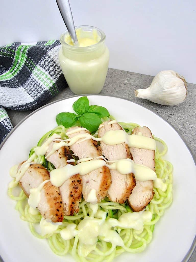 zucchini noodles with sliced chicken and alfredo sauce on top
