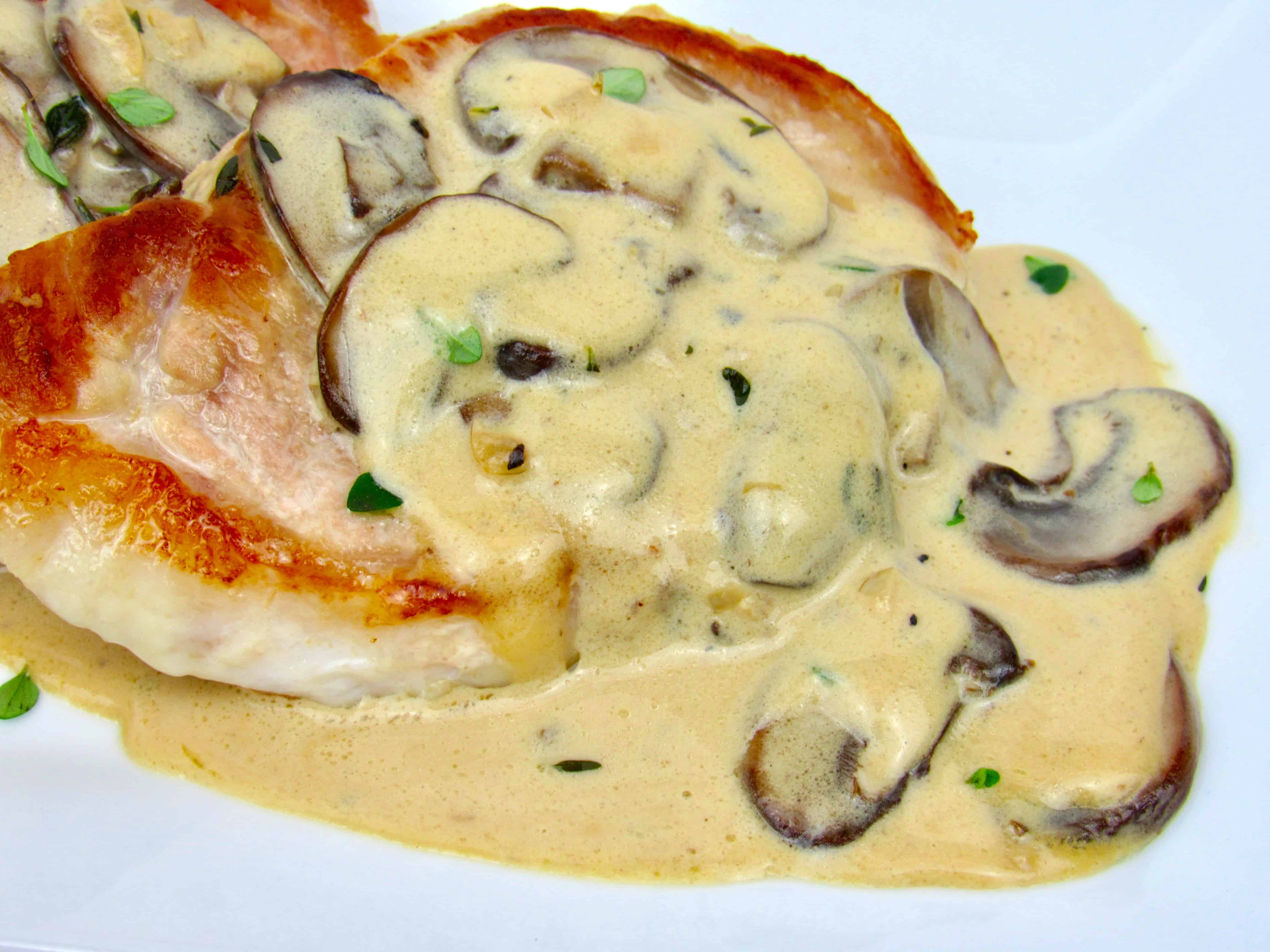 closeup of pork chop with mushroom gravy on top on white plate