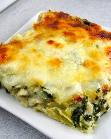 closeup spinach artichoke casserole slice on white plate