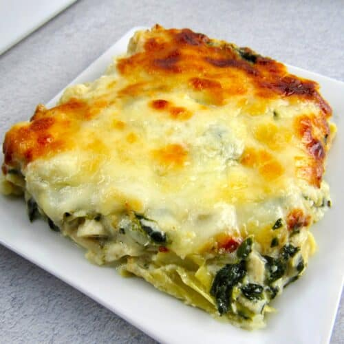closeup spinach artichoke casserole slice on white plate