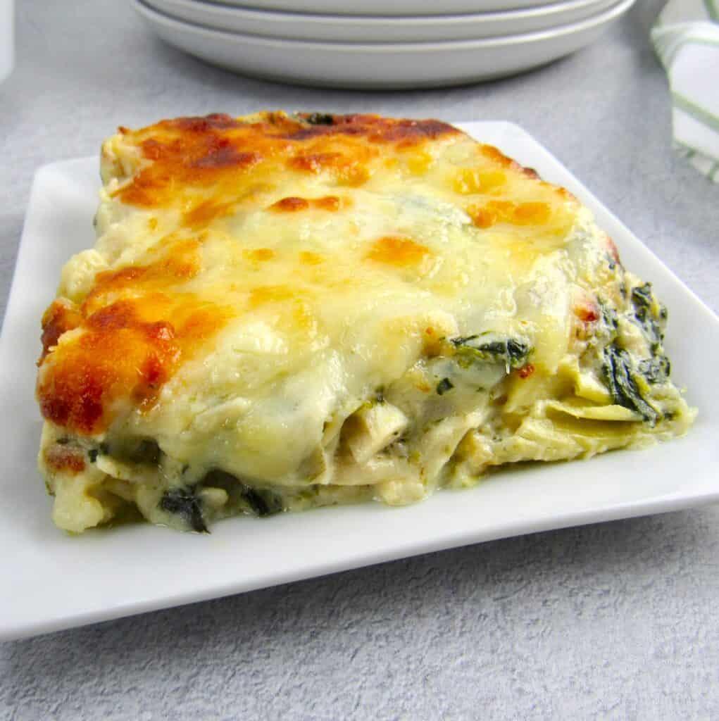 spinach artichoke casserole on white square plate
