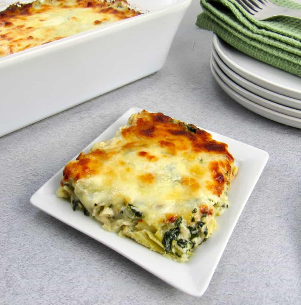 spinach artichoke casserole slice on white plate casserole in background