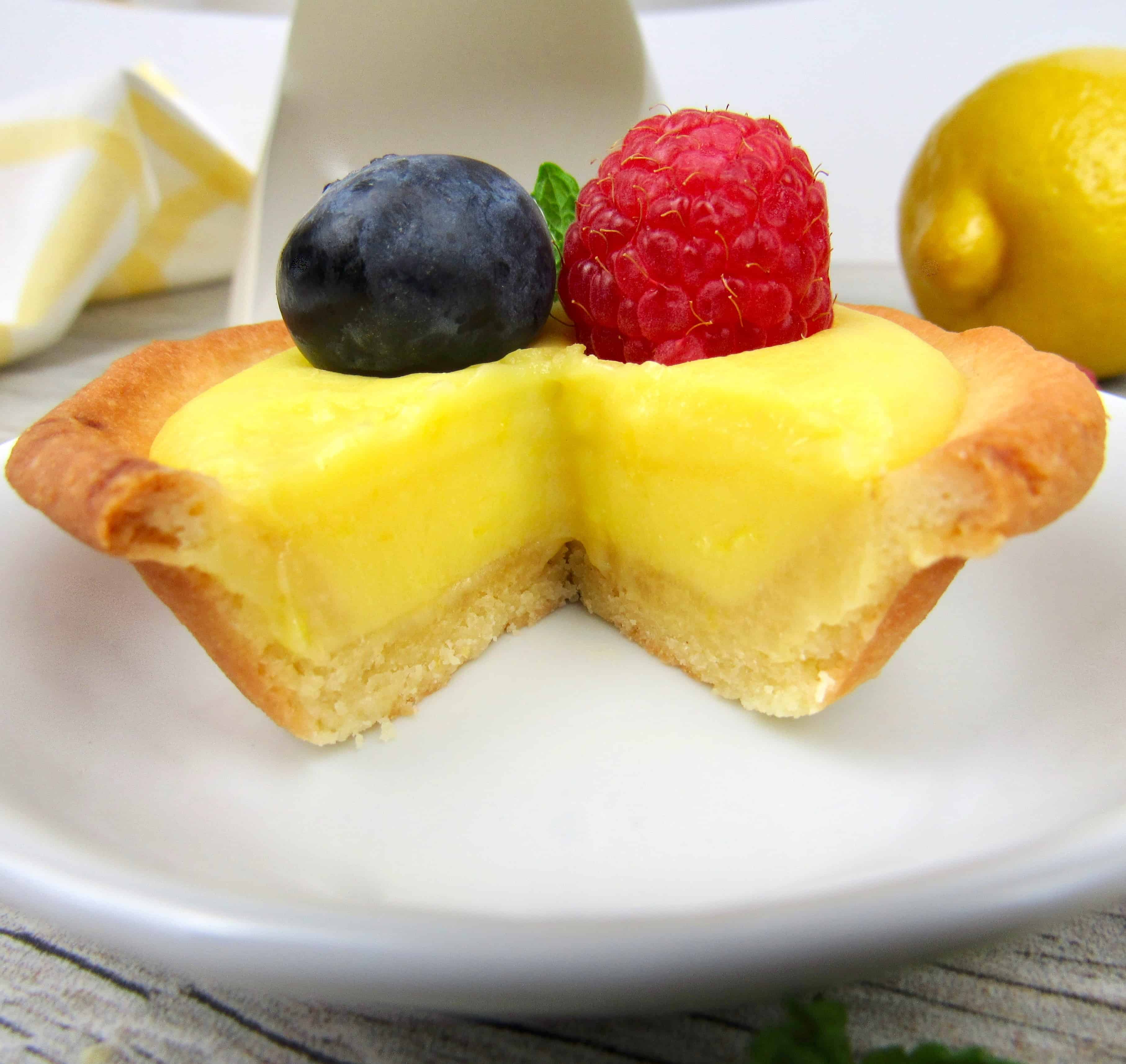 closeup of mini lemon curd tart with slice take out