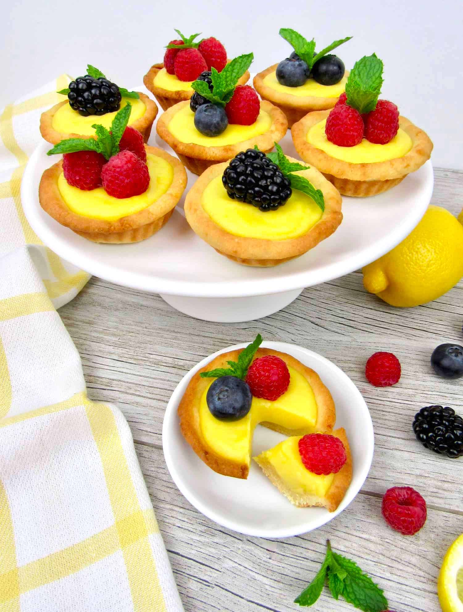 cake stand with mini lemon curd tarts with berries on top