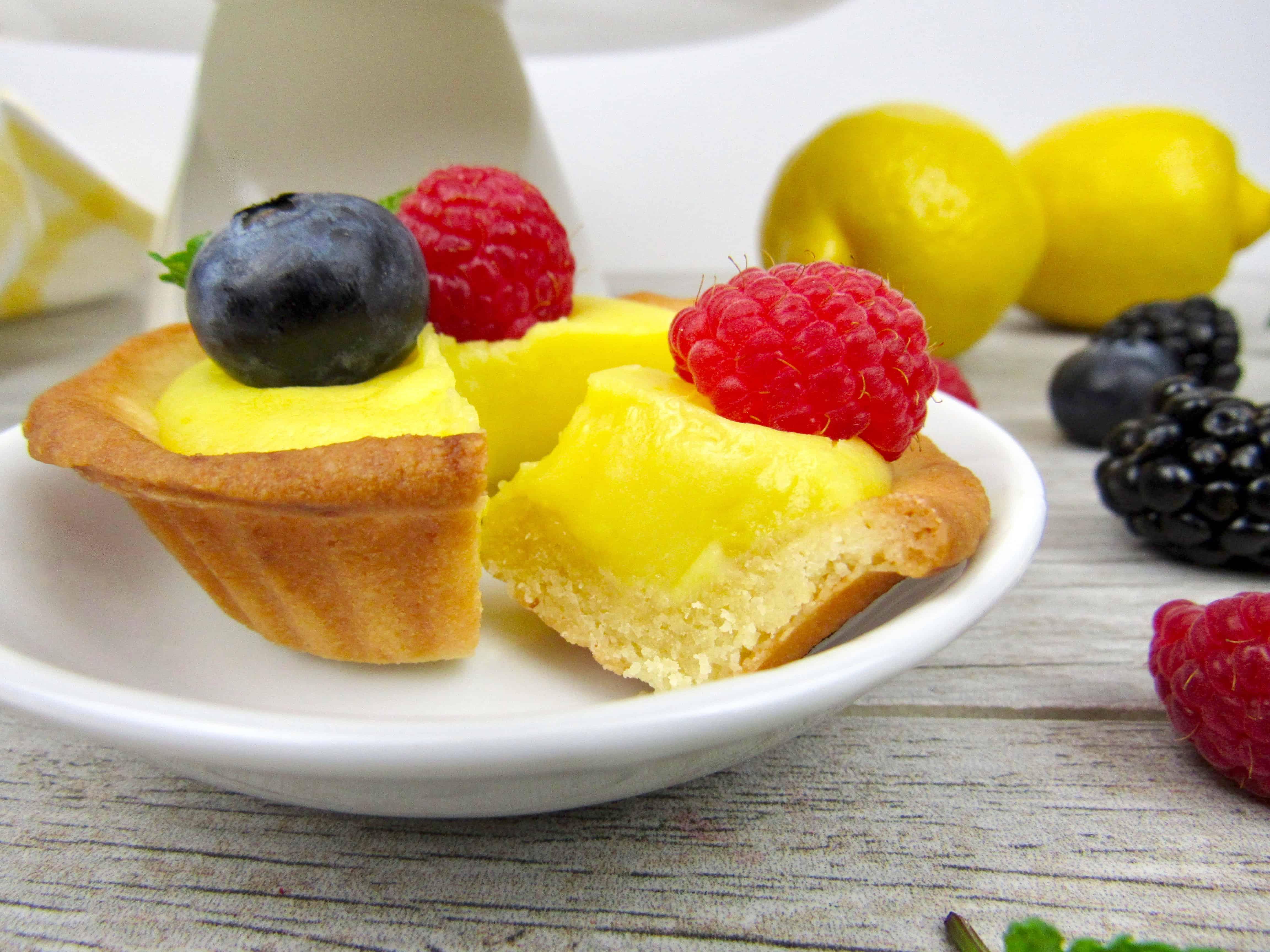 closeup of mini lemon curd tart with slice taken out
