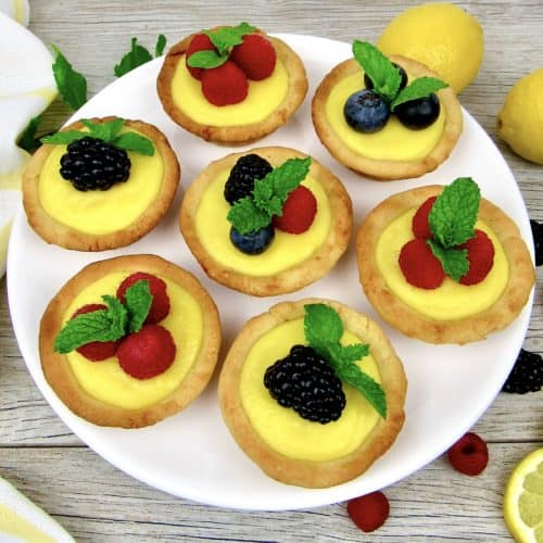 7 mini lemon curd tarts with berries on top