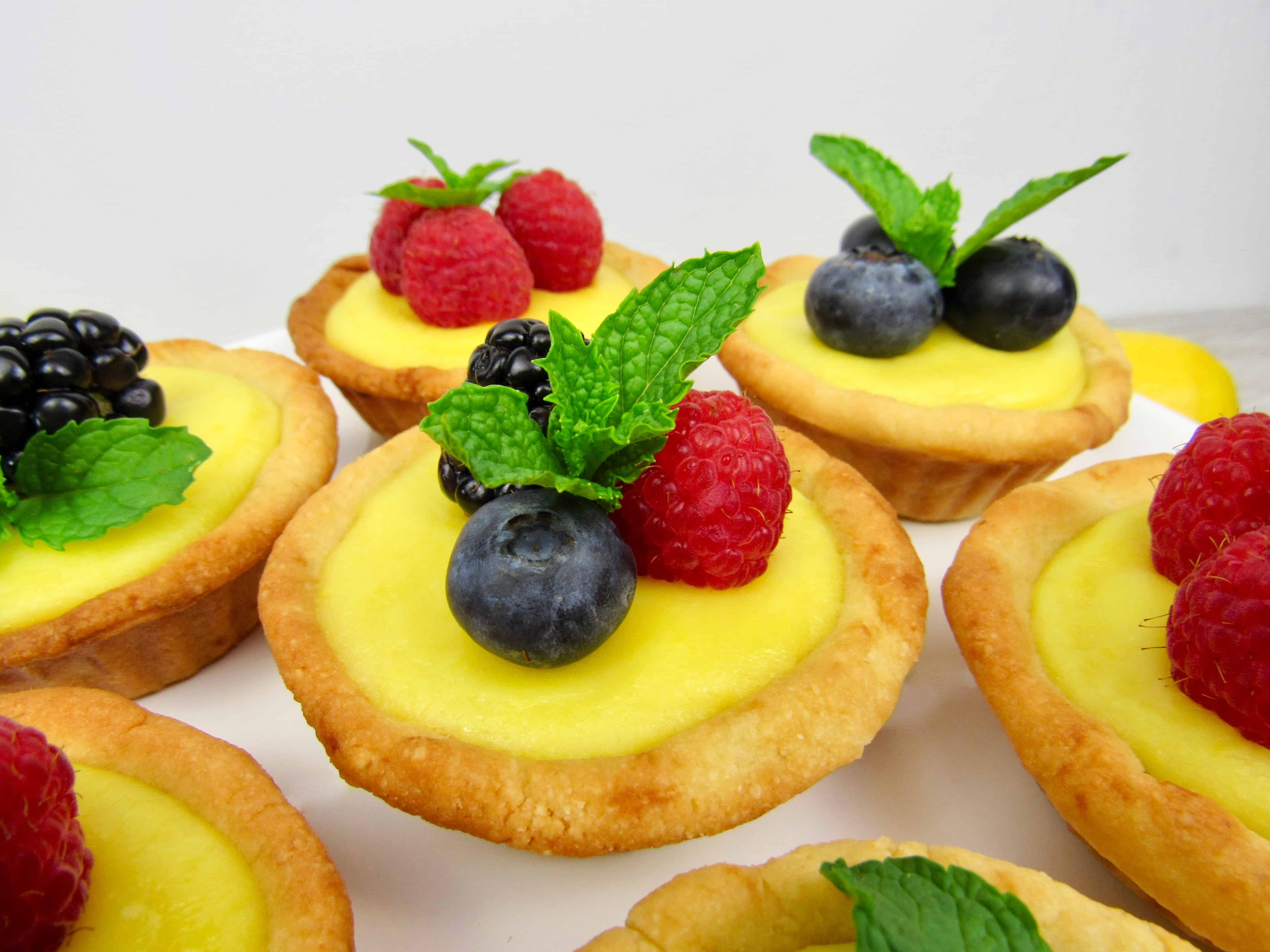 closeup of mini lemon curd tarts with berries on top