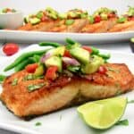 closeup salmon on plate topped with avocado salsa and lime wedge
