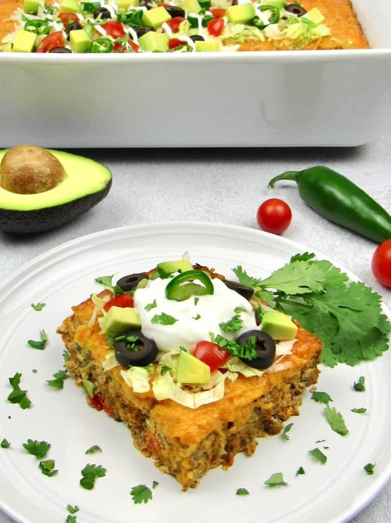 taco casserole slice closeup casserole in background