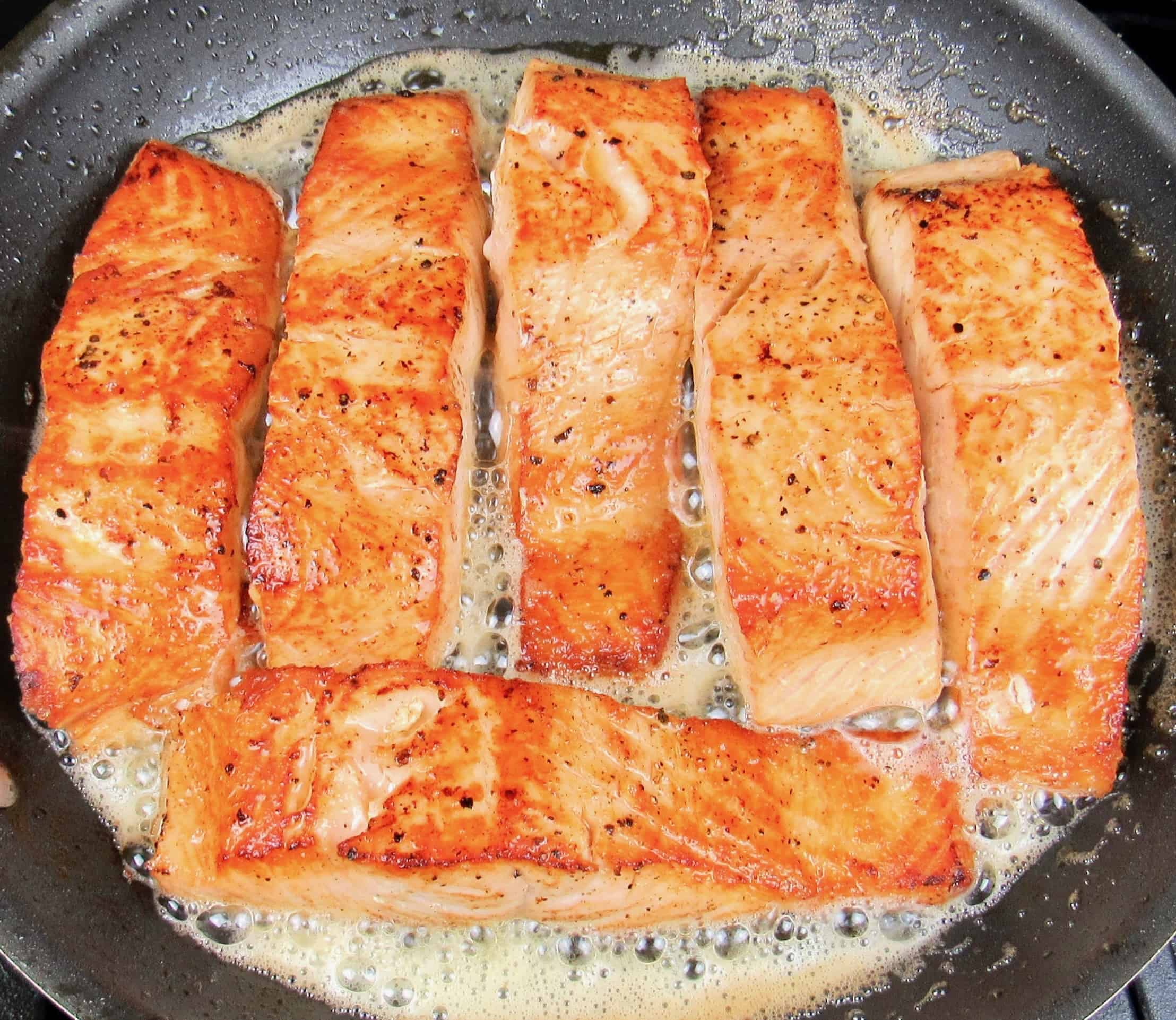 6 pieces of seared salmon in skillet