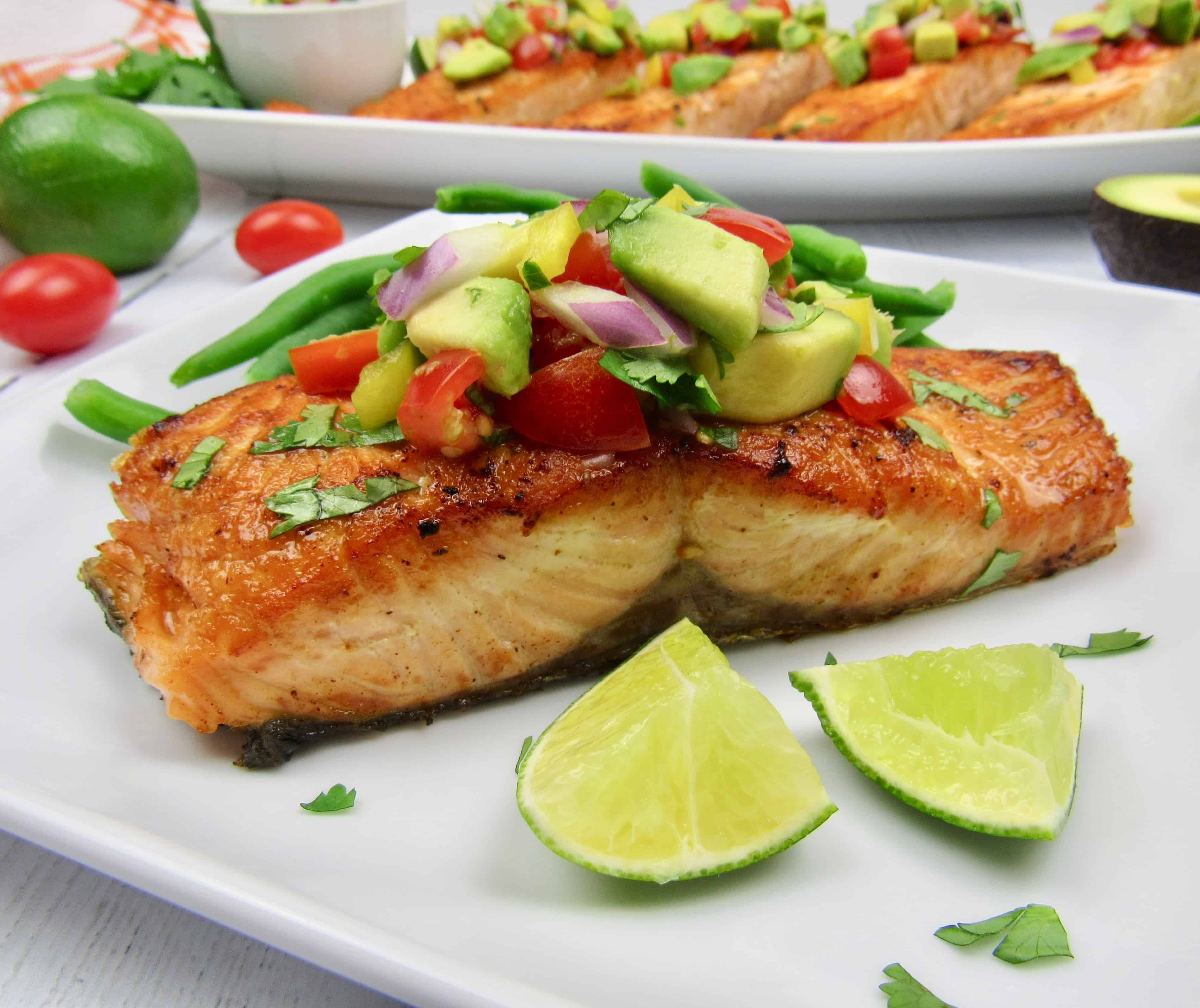 salmon on white plate with avocado salsa on top with lime wedges