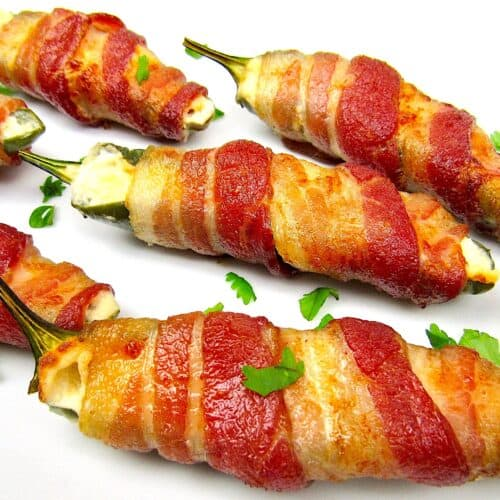 closeup of bacon wrapped jalapeño poppers on white plate