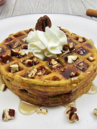 Keto Pumpkin Chaffles on plate with syrup and nuts