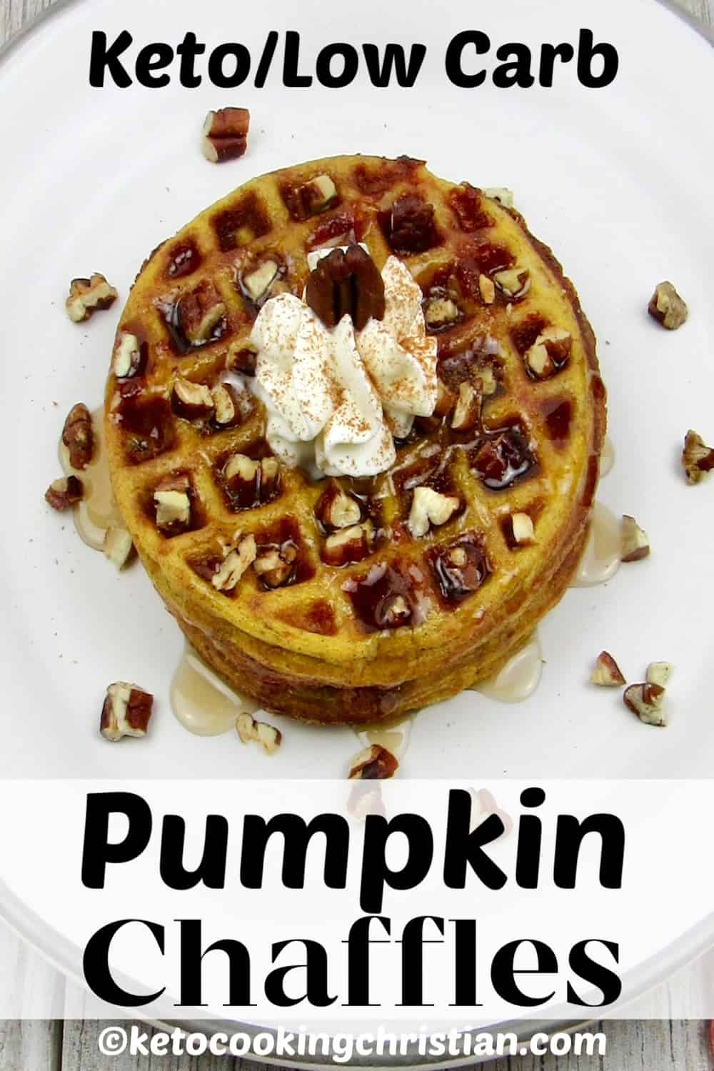 pumpkin chaffles on white plate with syrup, whip cream and chopped pecans