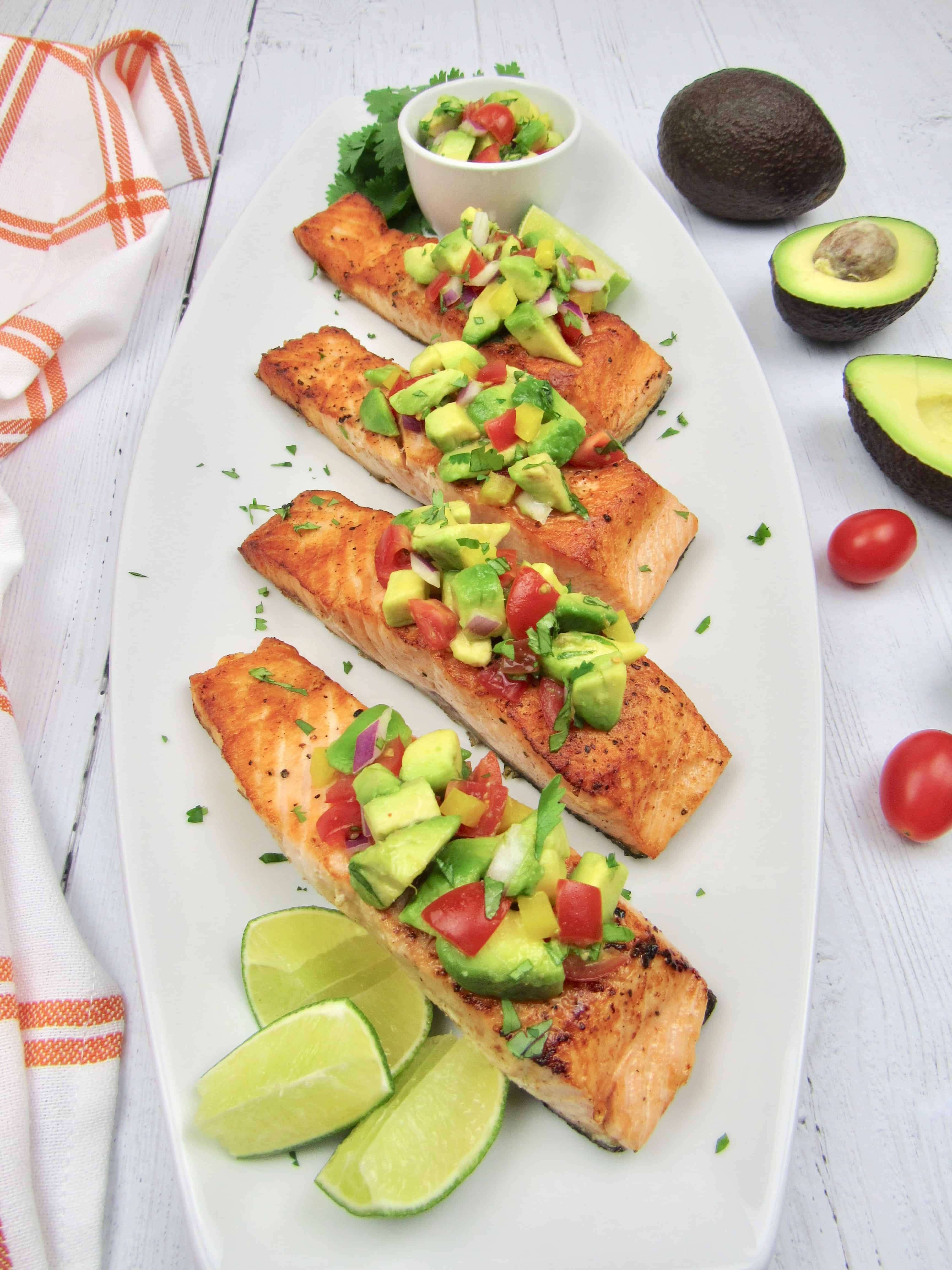 4 pieces salmon with avocado salsa over the top with lime wedges