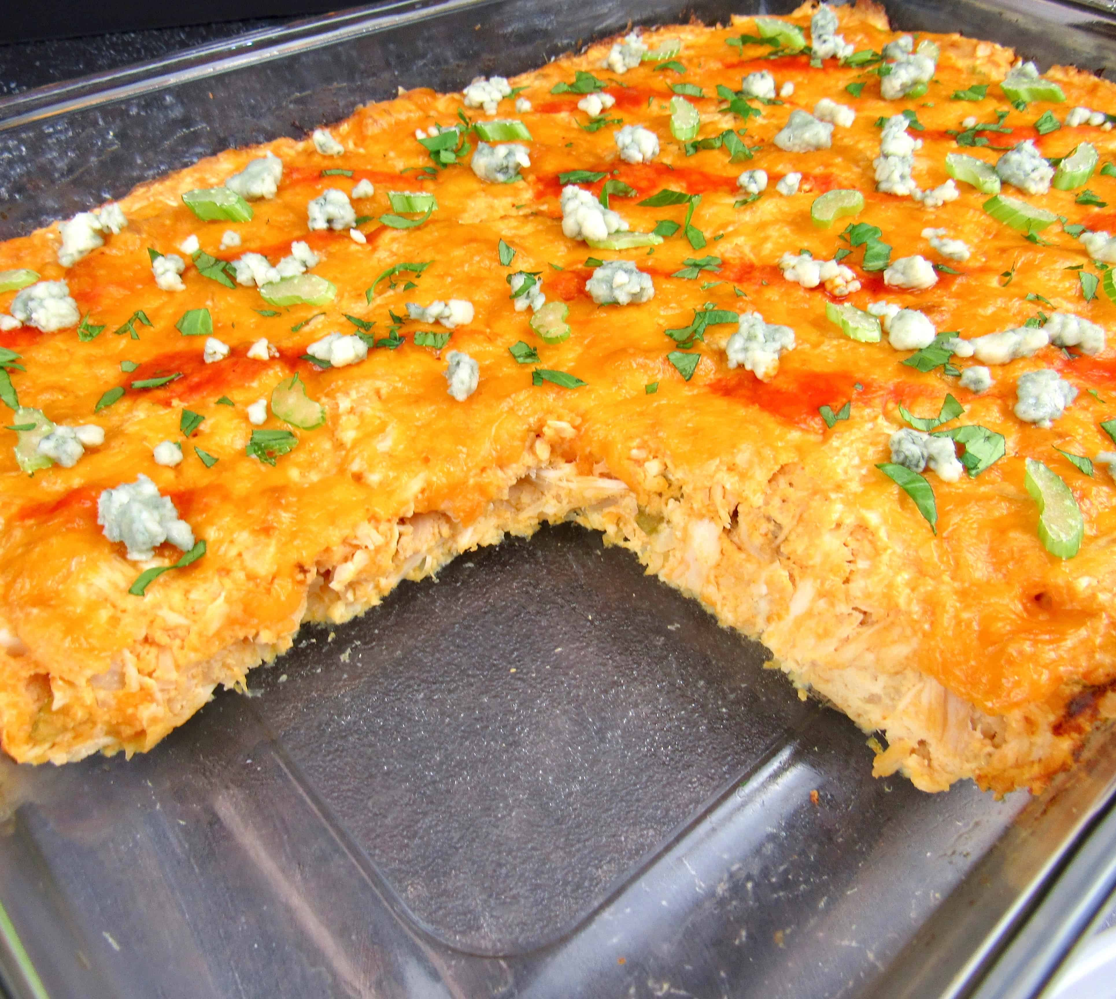 buffalo chicken casserole in glass baking dish with slice missing
