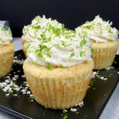 closeup of frosted coconut cupcakes with lime zest and coconut flakes