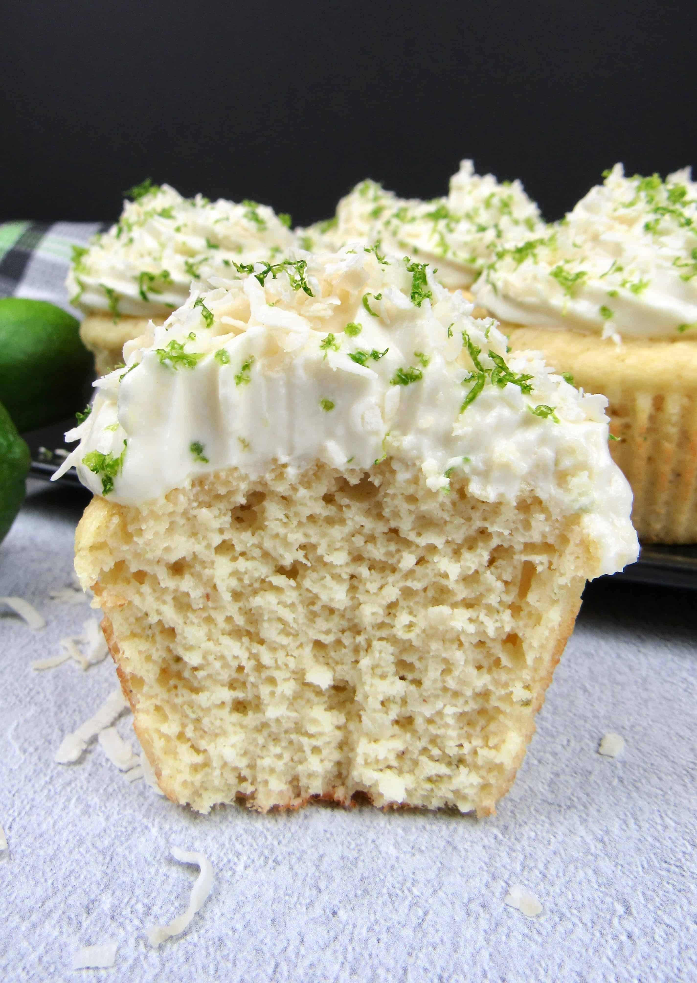 closeup of coconut lime cupcake on a black square plate with frosting, lime zest and coconut flakes on top cut open