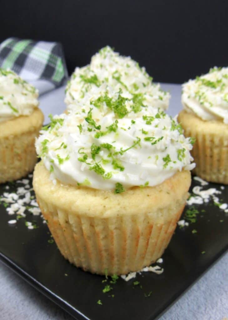 closeup of coconut lime cupcake on a black square plate with frosting, lime zest and coconut flakes on top