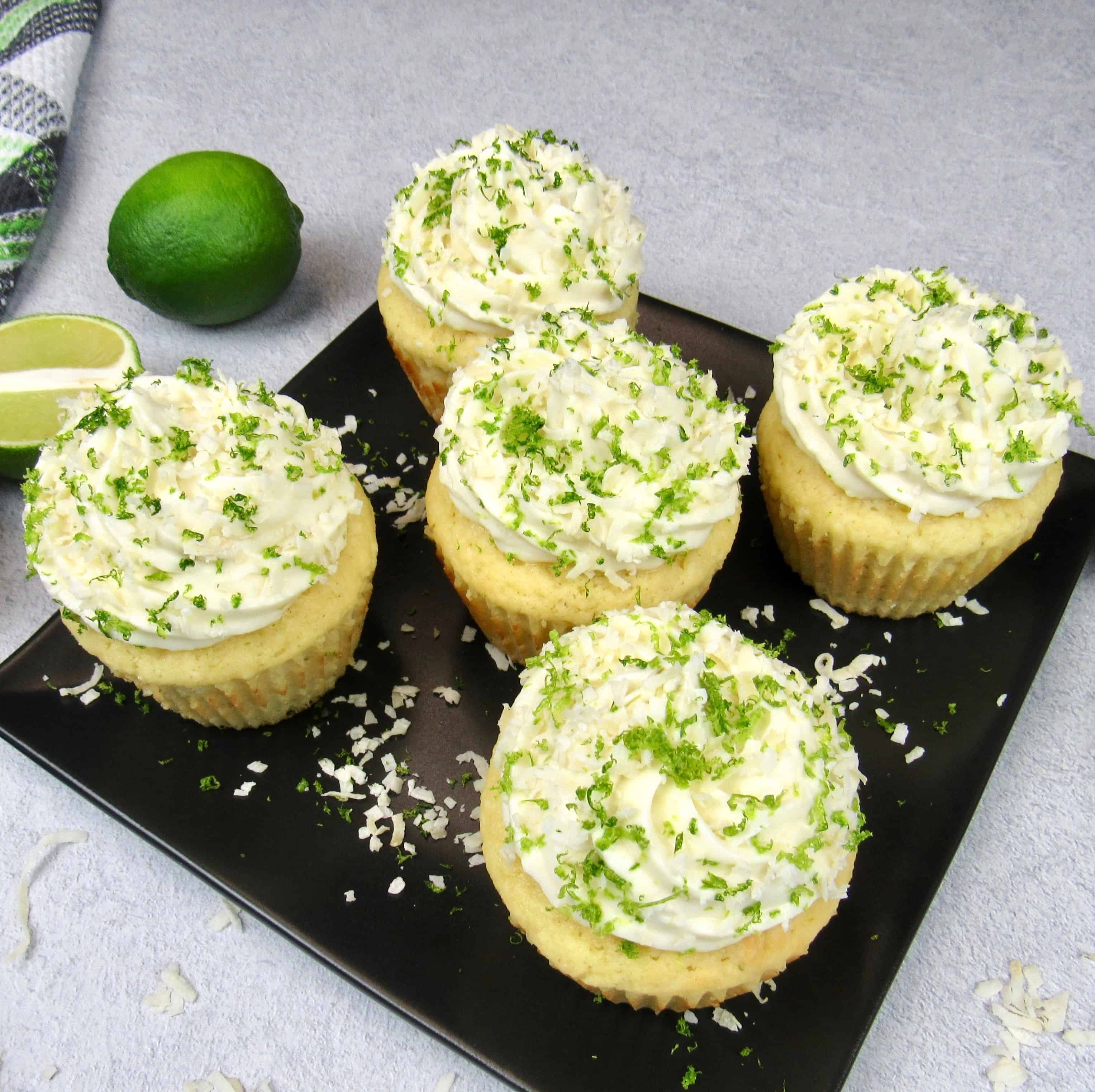 5 coconut lime cupcakes on a black square plate with frosting, lime zest and coconut flakes on top