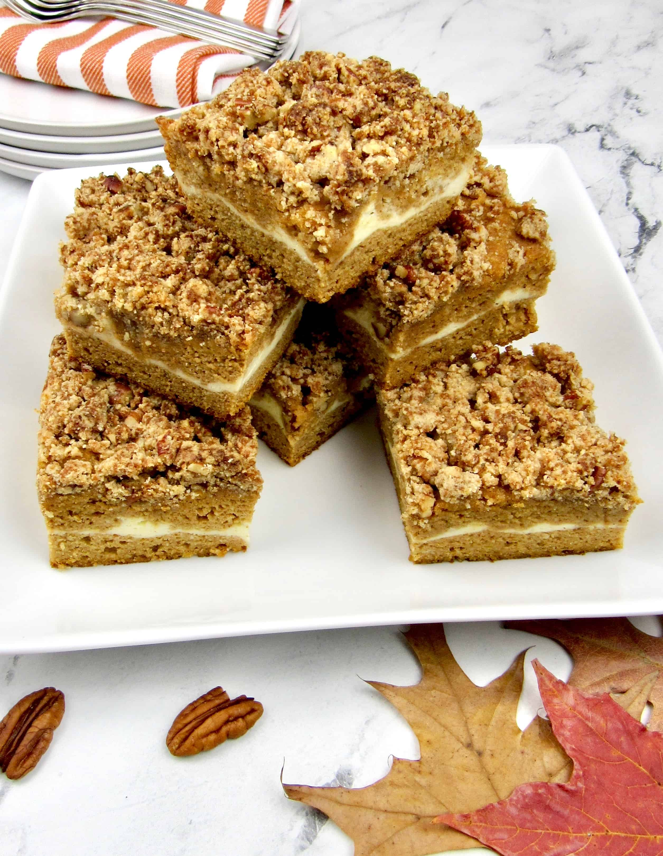 slices of pumpkin coffee cake stacked up on a square plate