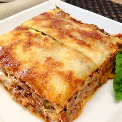 slice of zucchini lasagna with basil garnish on white plate