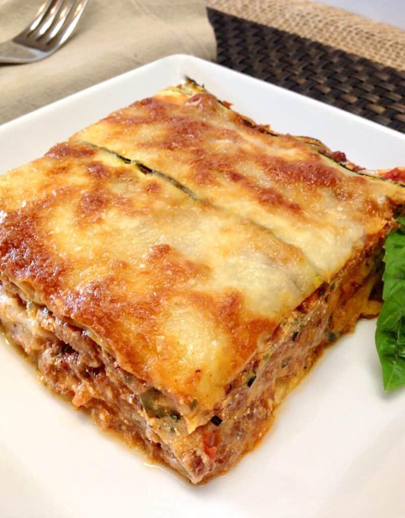 slice of zucchini lasagna with basil garnish on white plate