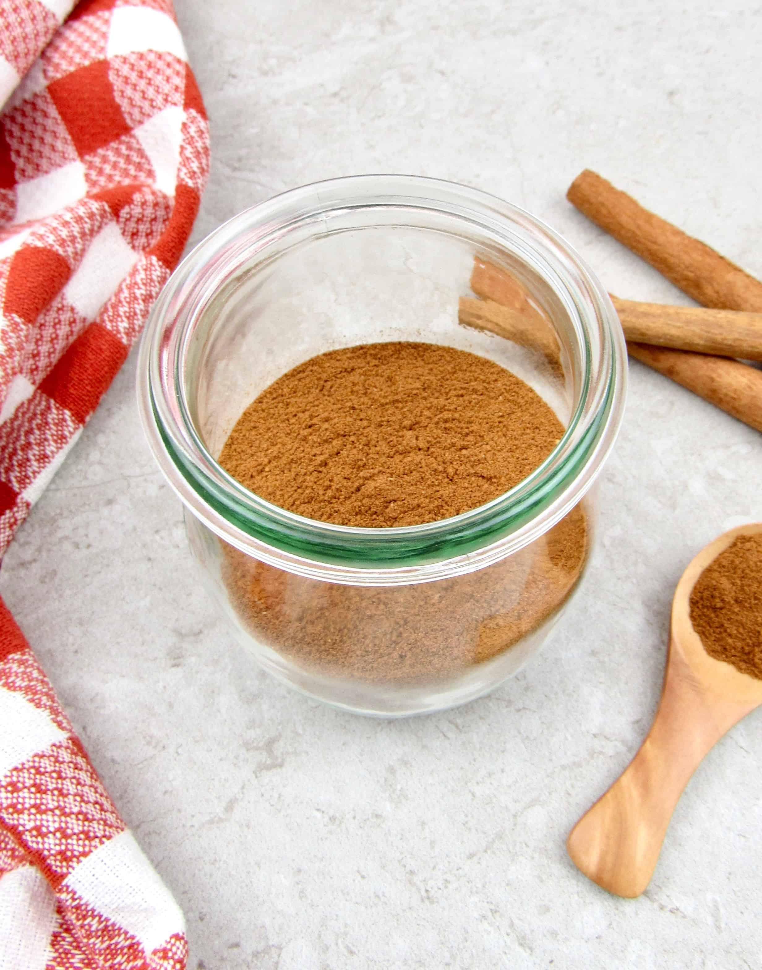 apple pie spice mixture in glass jar with cinnamon sticks on background