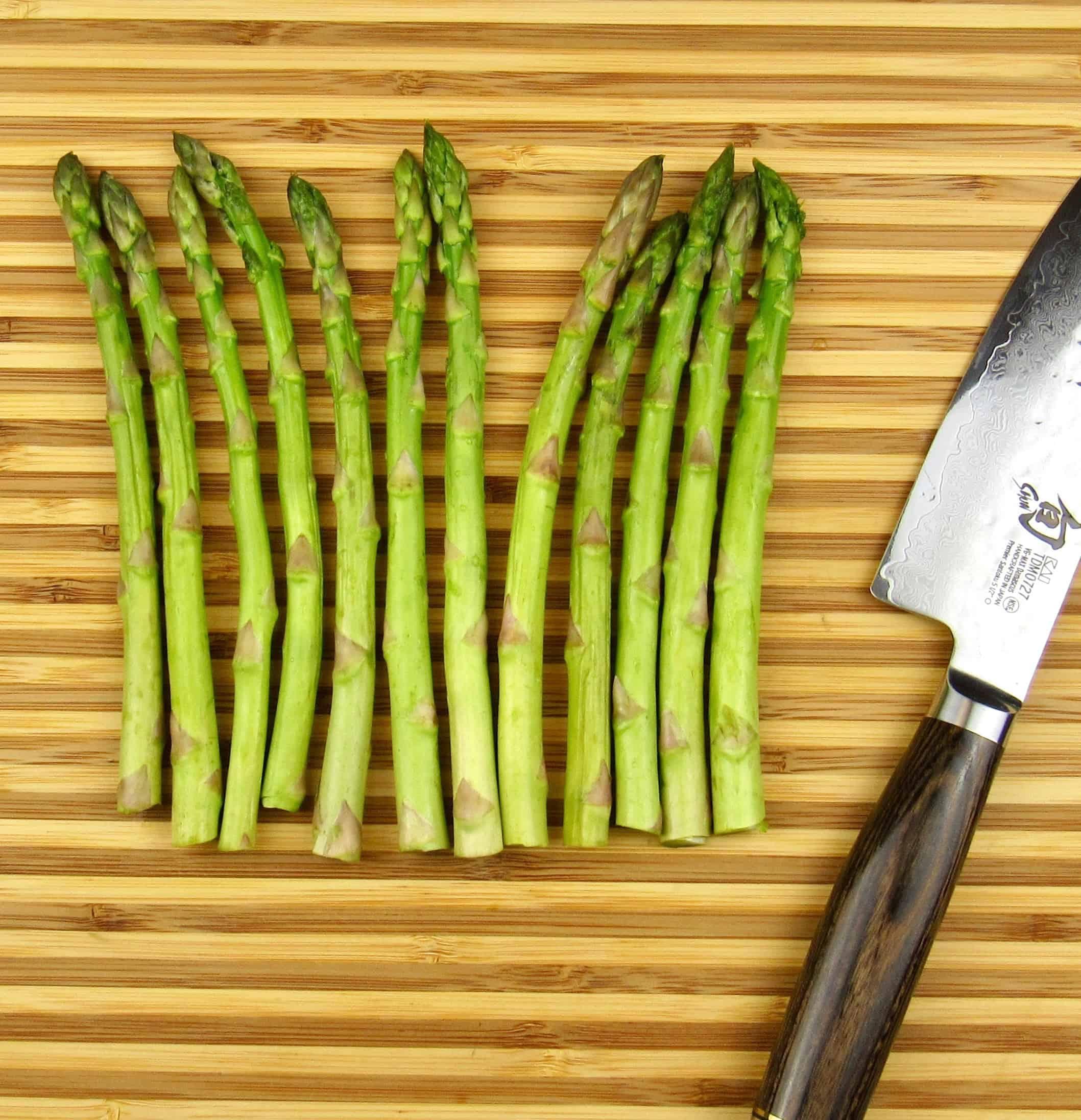 cut asparagus on cutting board with knife