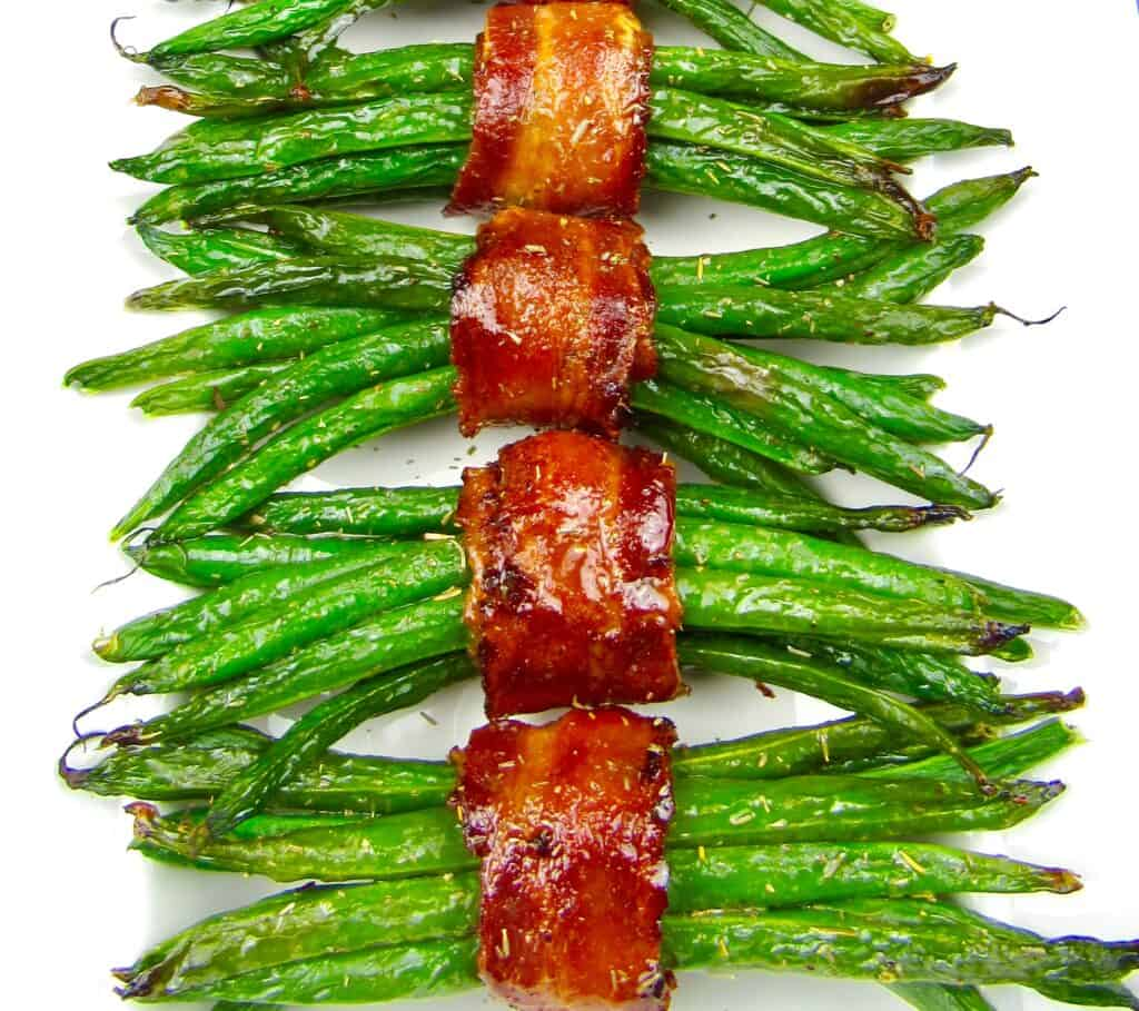4 bundles of bacon wrapped green beans on white plate