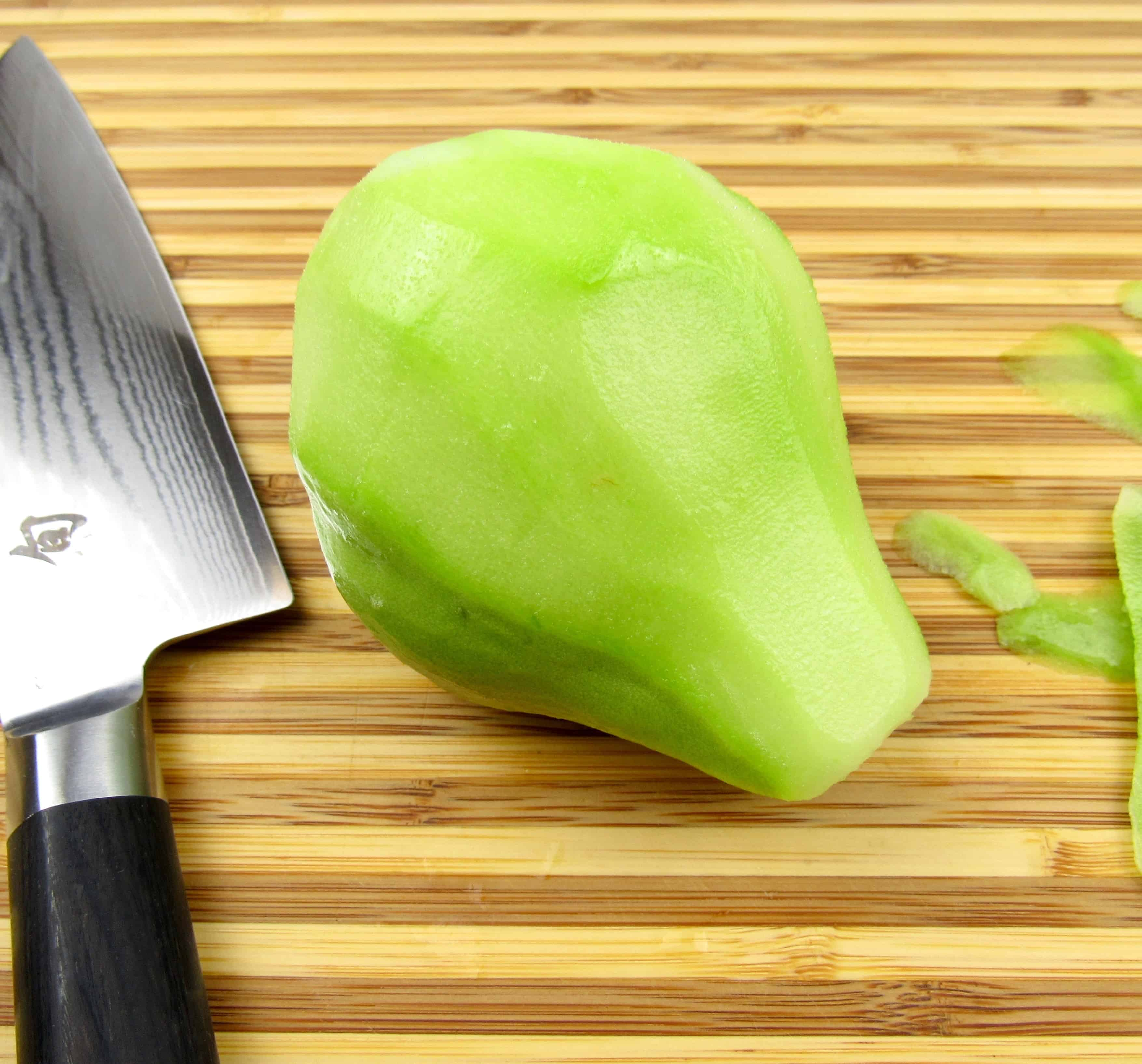 peeled chayote squash on butting board with knife