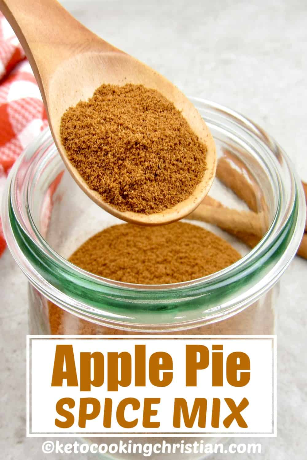 apple pie spice mix being held over glass jar in wooden spoon
