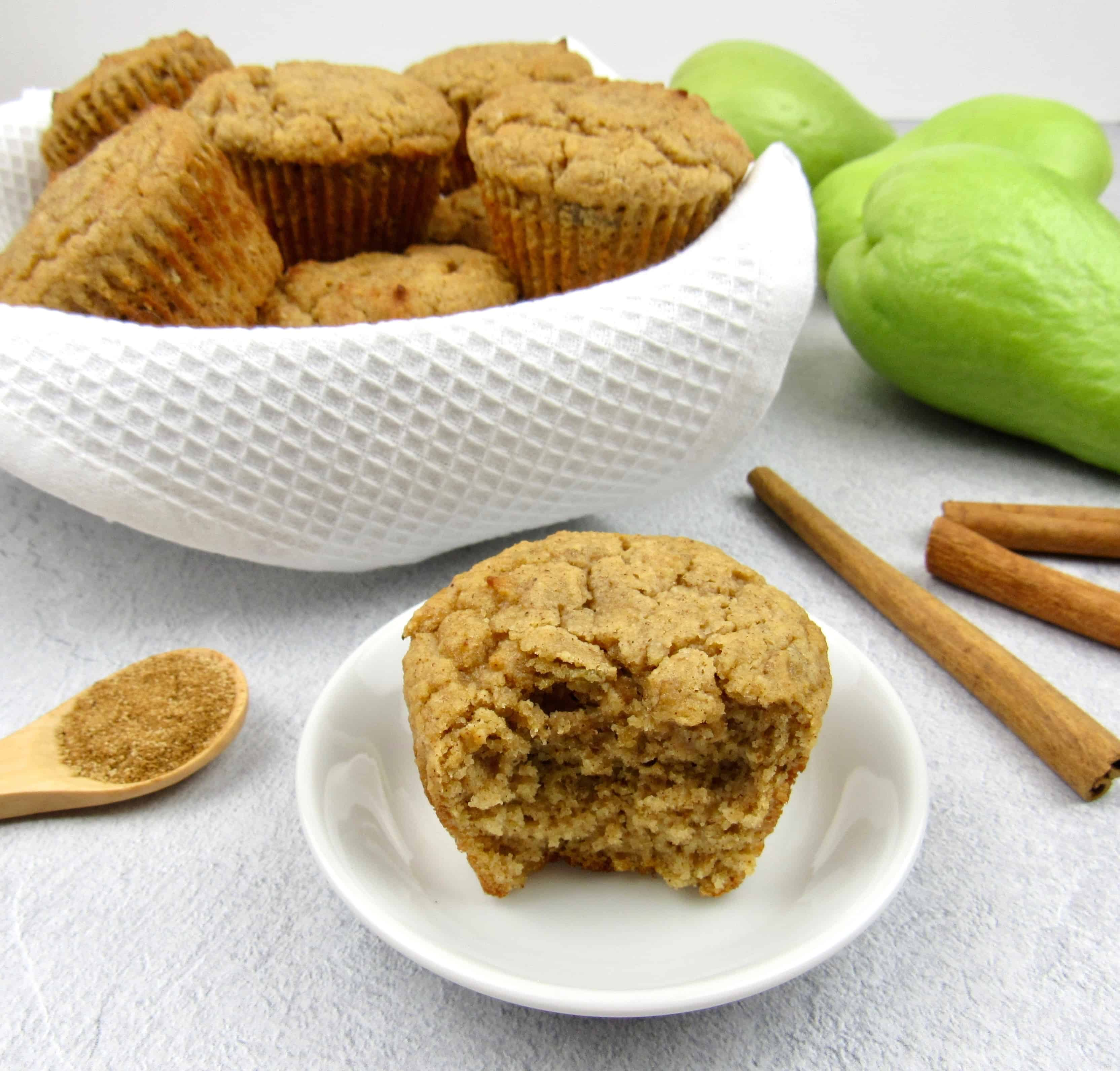 keto mock apple muffin with bite taken out and basket with muffins in the background
