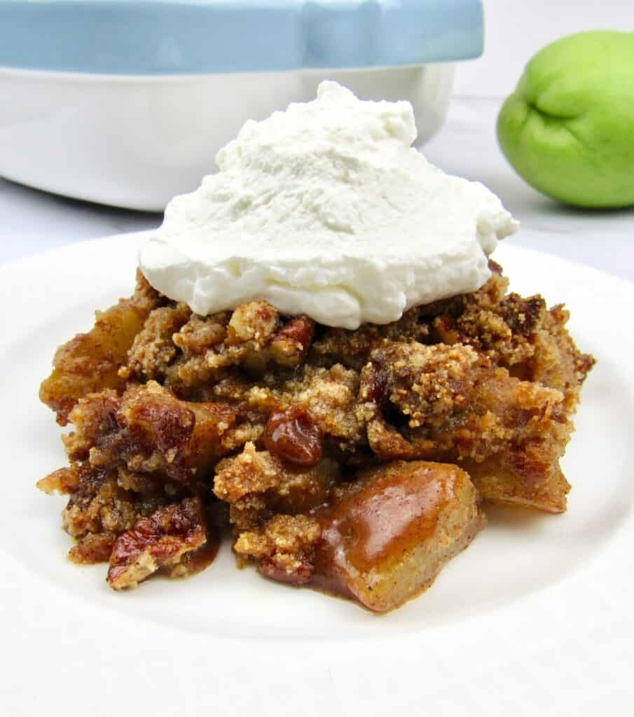 closeup of mock apple crumble on white plate with whip cream on top