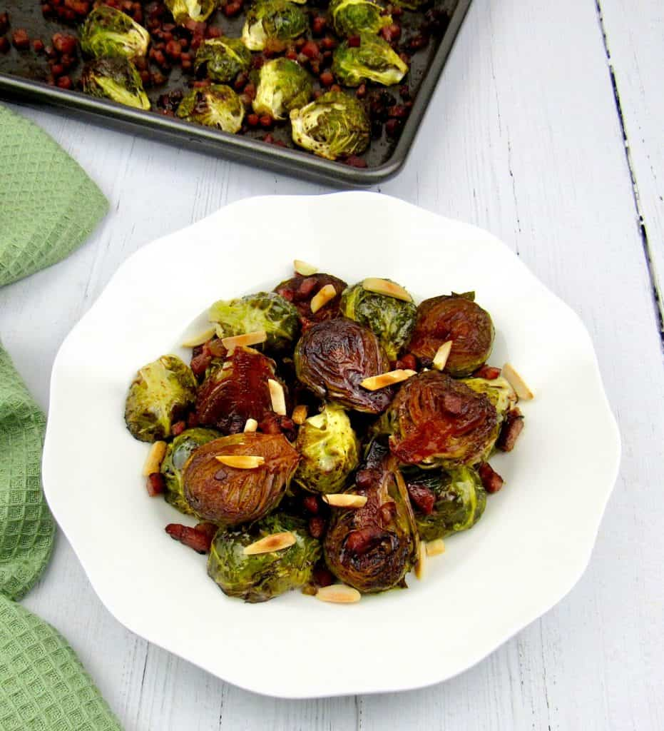 overhead view of brussels sprouts in white dish with sheet pan in background