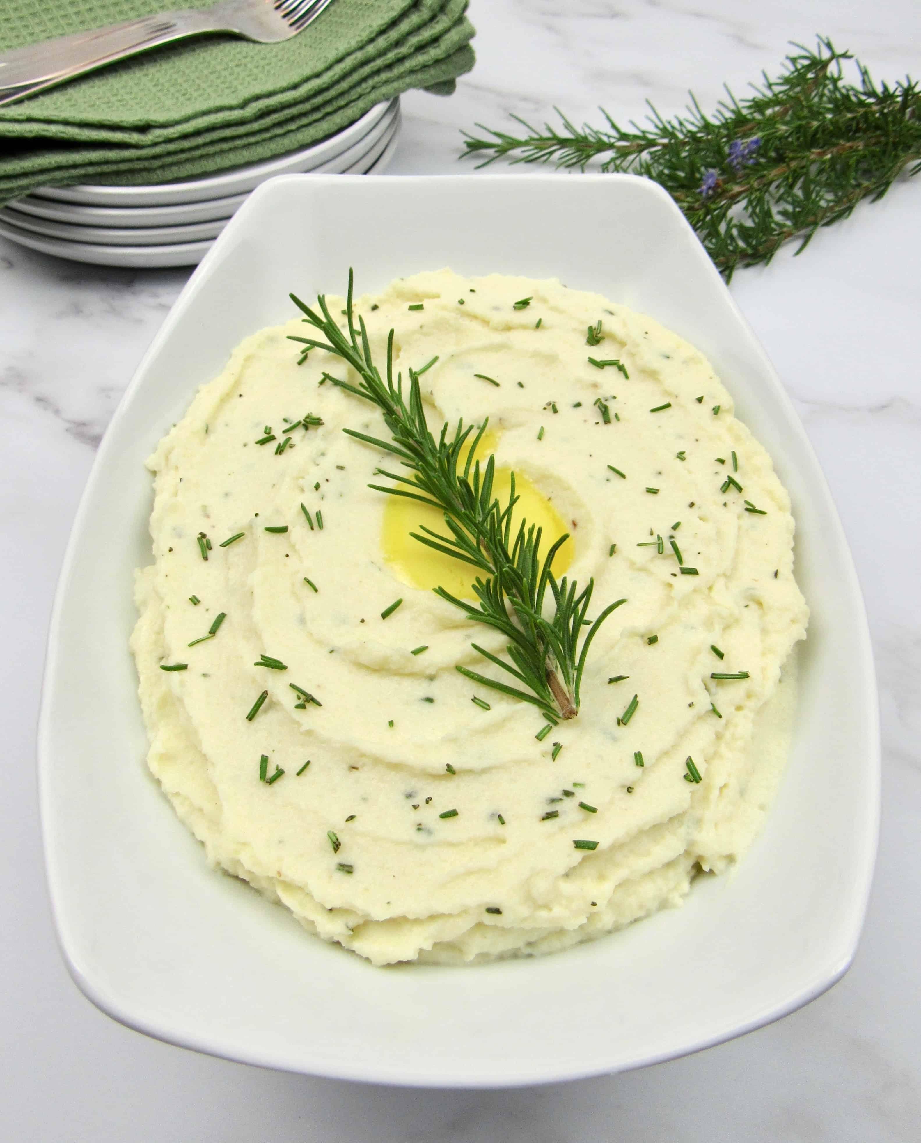 white bowl with mashed cauliflower with rosemary sprig garnish
