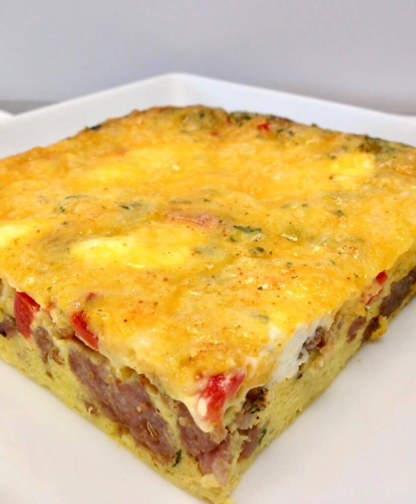 slice of sausage, egg and pepper casserole on white plate