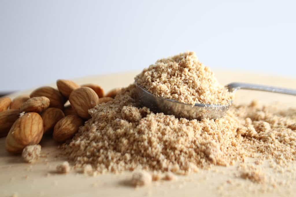 almond flour on cutting board with whole almonds and wooden spoon