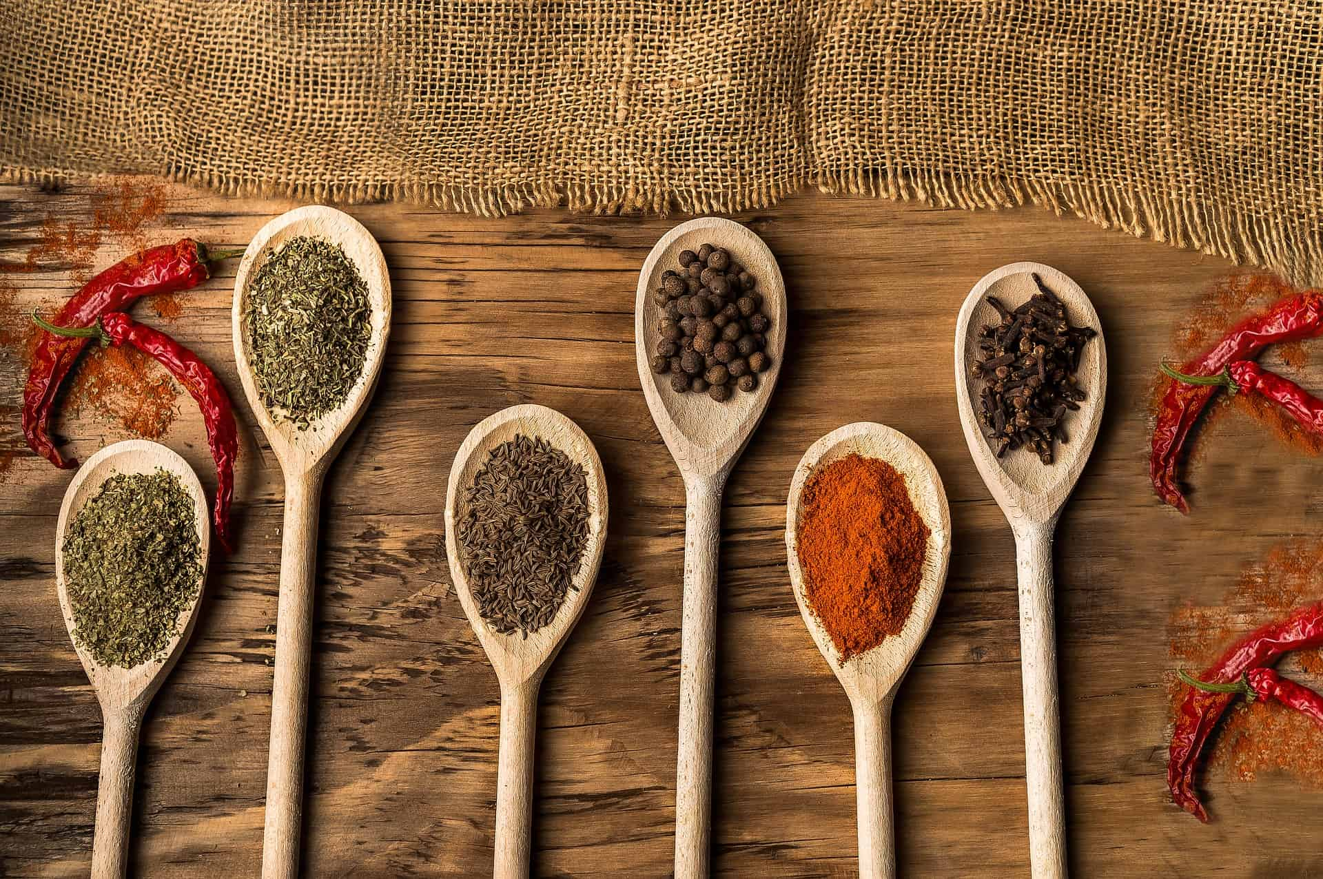wooden spoons on cutting board filled with spices