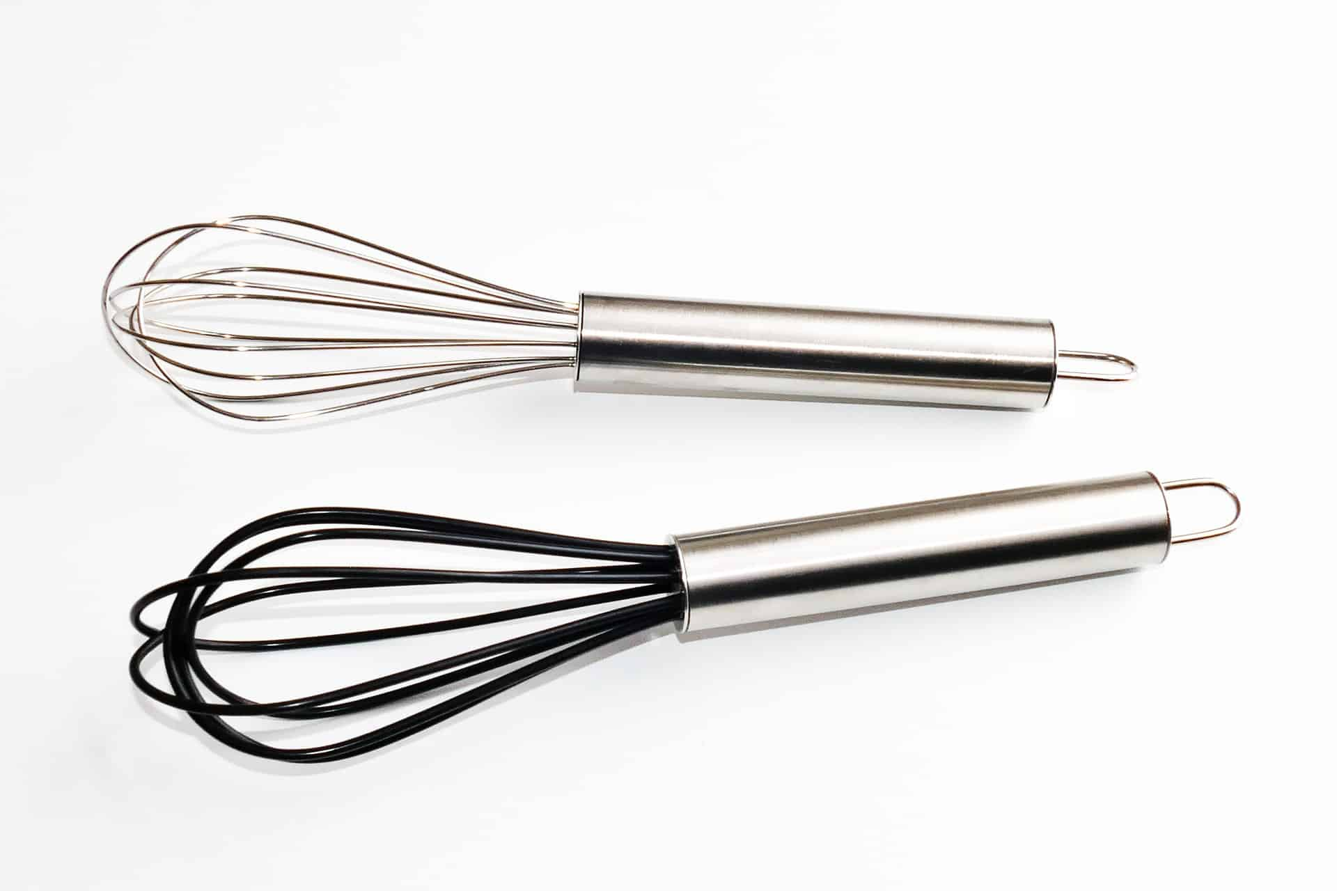 2 whisks on a white table
