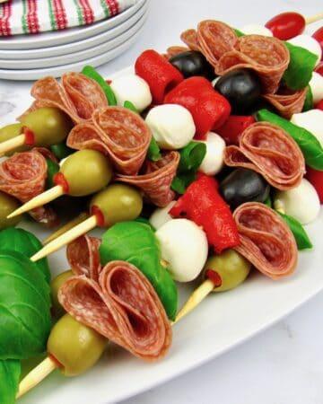 Italian antipasti skewers on white platter