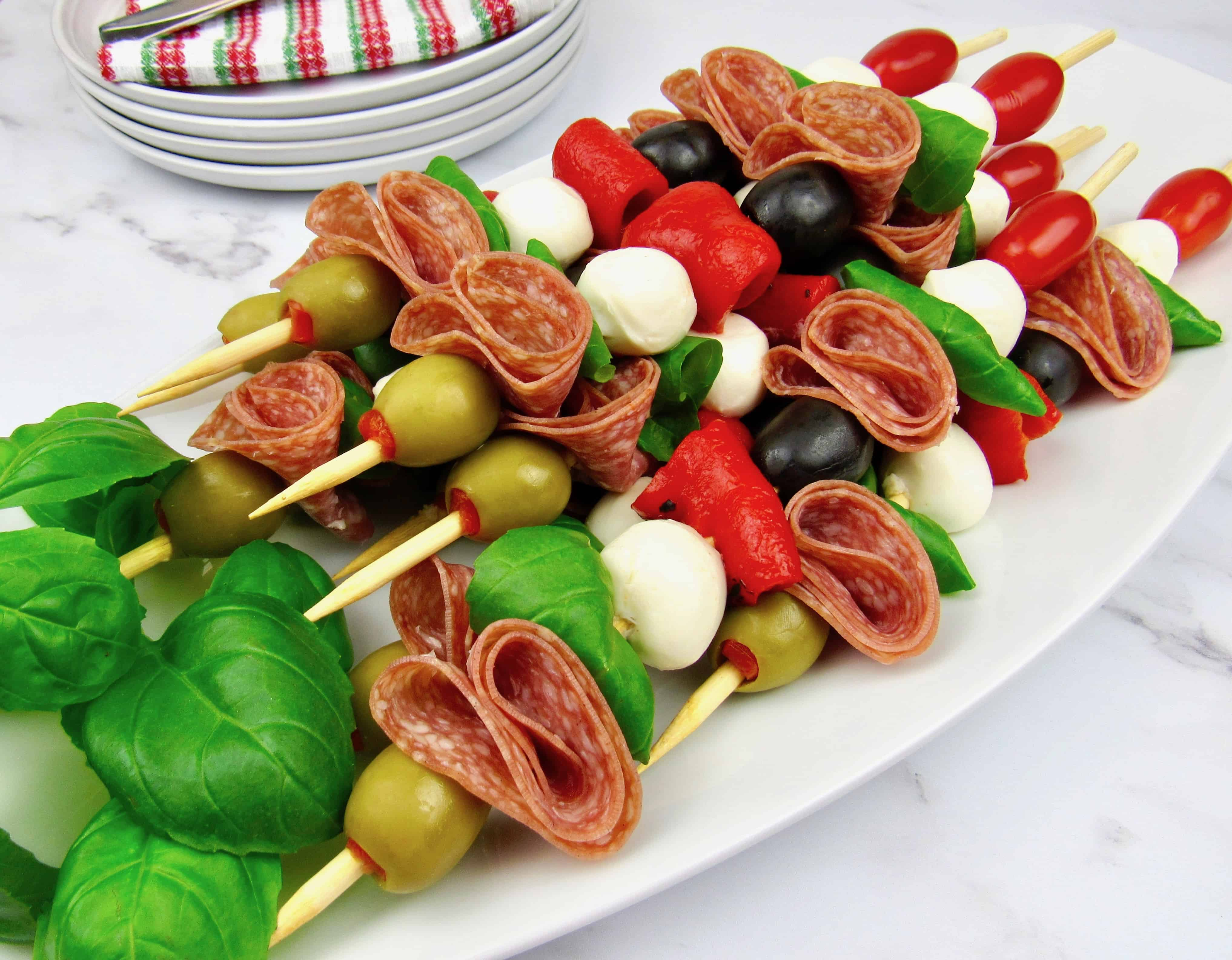 Italian antipasti skewers on white platter