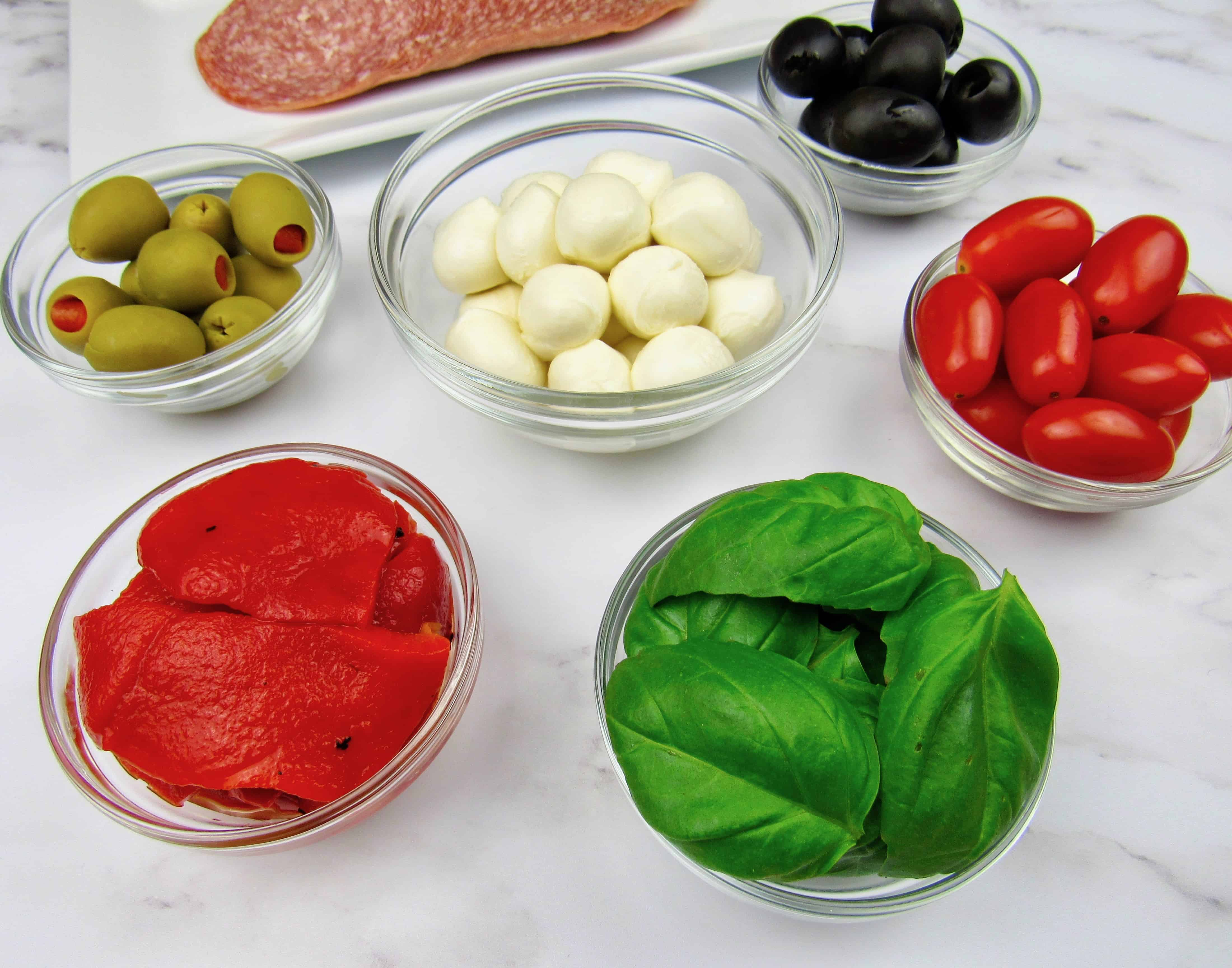 closeup of ingredients for antipasti skewers in little glass bowls