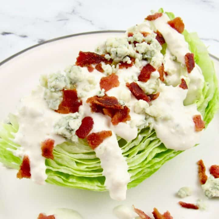 blue cheese dressing over iceberg lettuce wedge