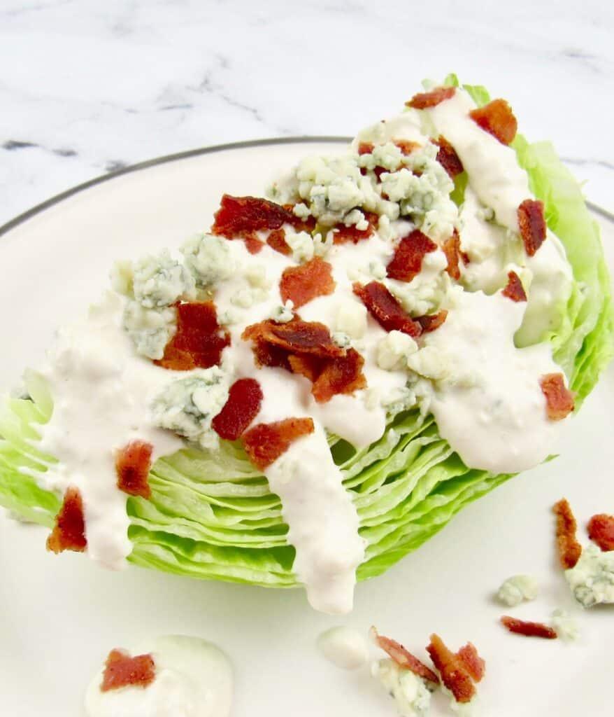 blue cheese dressing over iceberg lettuce wedge