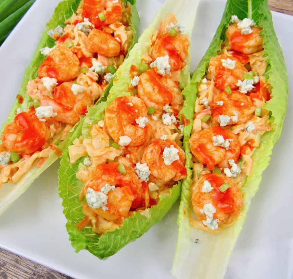buffalo shrimps in lettuce wraps on white plate