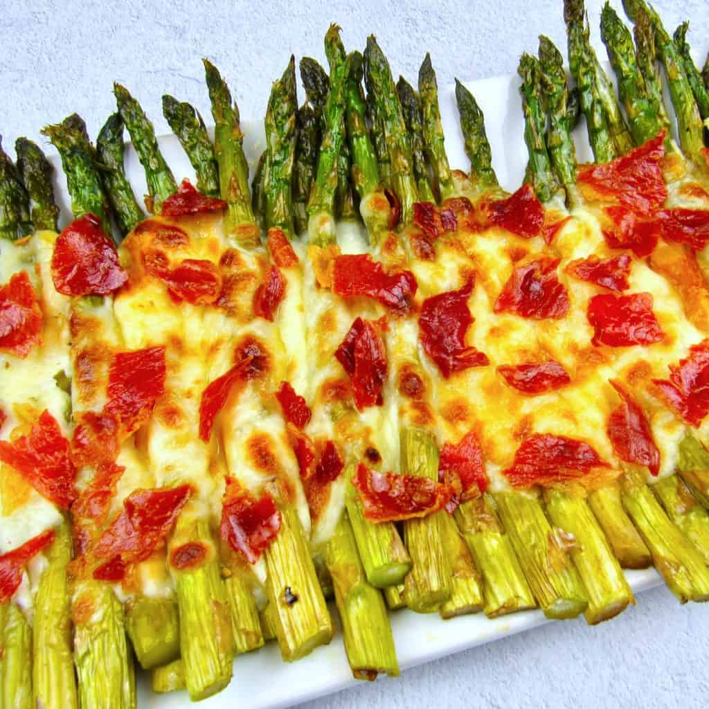 overhead closeup roasted asparagus on sheet pan with melted cheese and crispy prosciutto