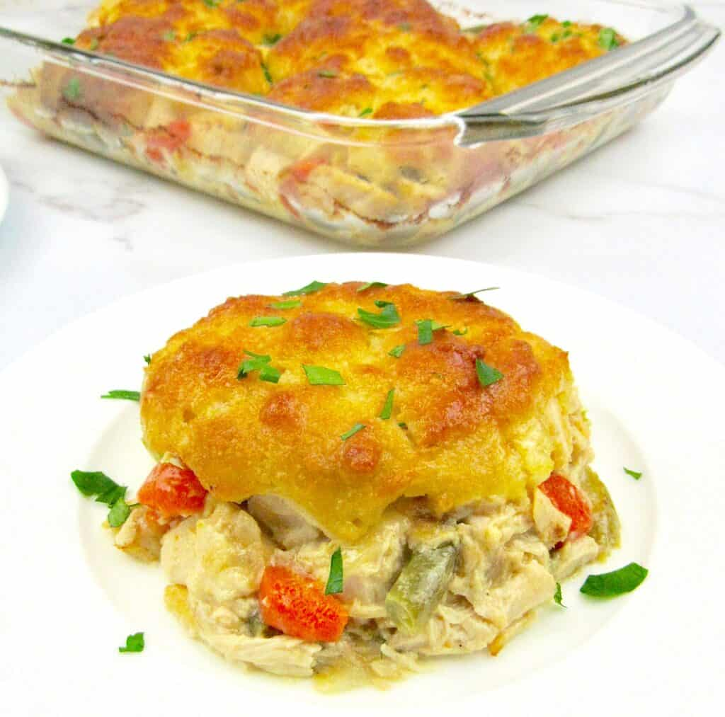 piece of chicken pot pie casserole on white plate with casserole in the background