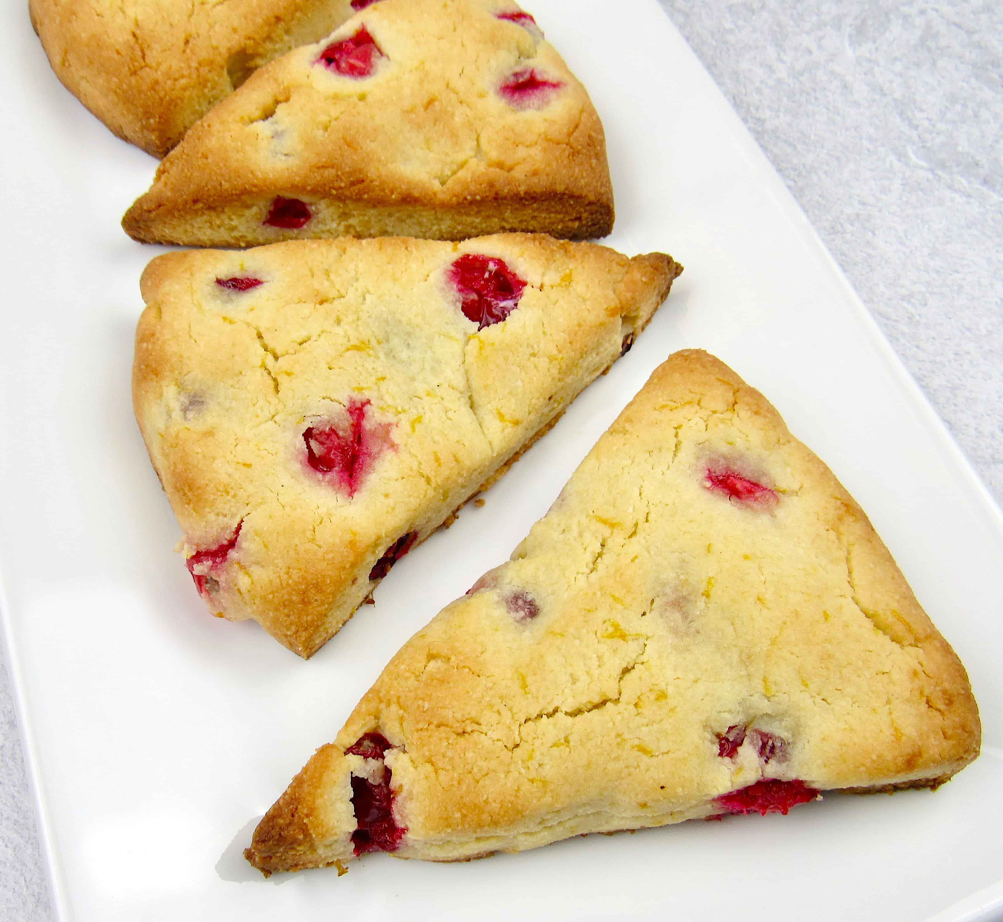 overhead view of 4 cranberry scones on white plate