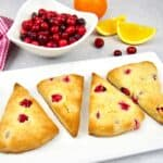 4 cranberry scones on while plate with cranberries in background